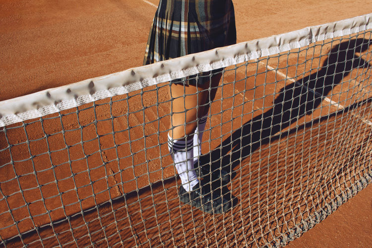 Low section of woman standing on a tenis court