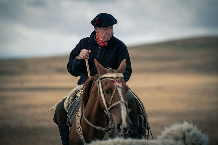 Mature man riding horse on land