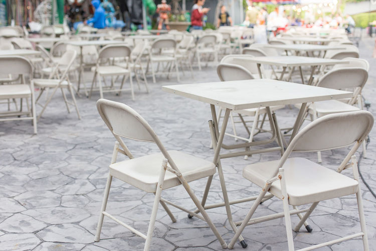 Table and chairs of an outdoor cafe In europe Chair Seat Table Empty Absence Day Cafe Sidewalk Cafe Arrangement White Color Furniture Outdoors Business Architecture Focus On Foreground Restaurant Flooring Chairs Europe Incidental People Large Group Of Objects Setting