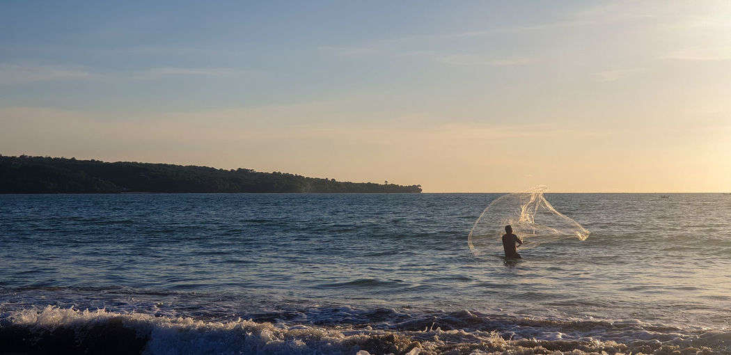 Rear view of fisherman throwing fishing net in sea against sky