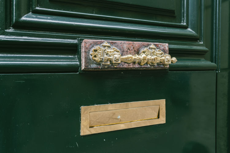 Close-up of mailbox on closed door