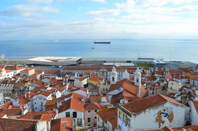Aerial view of townscape by sea against sky