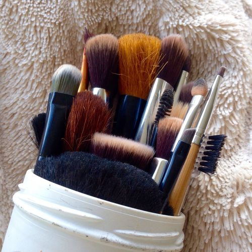 Close-up of various make-up brushes in container on fur