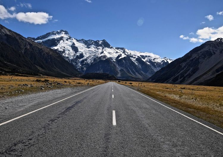 Empty road leading towards snowcapped mountains against blue sky