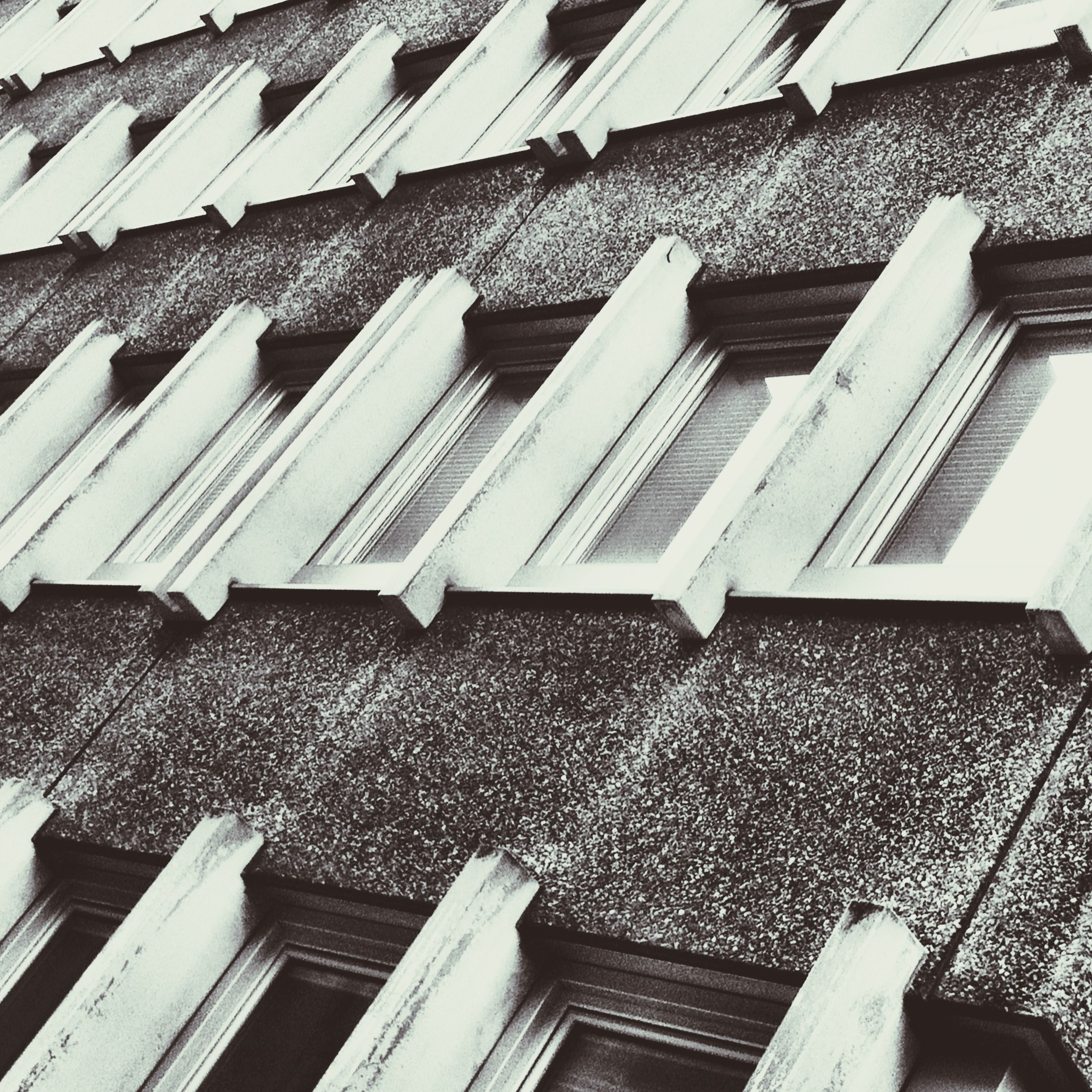 building exterior, architecture, built structure, low angle view, building, window, roof, residential building, residential structure, day, outdoors, city, no people, in a row, house, pattern, sky, high angle view, balcony, sunlight