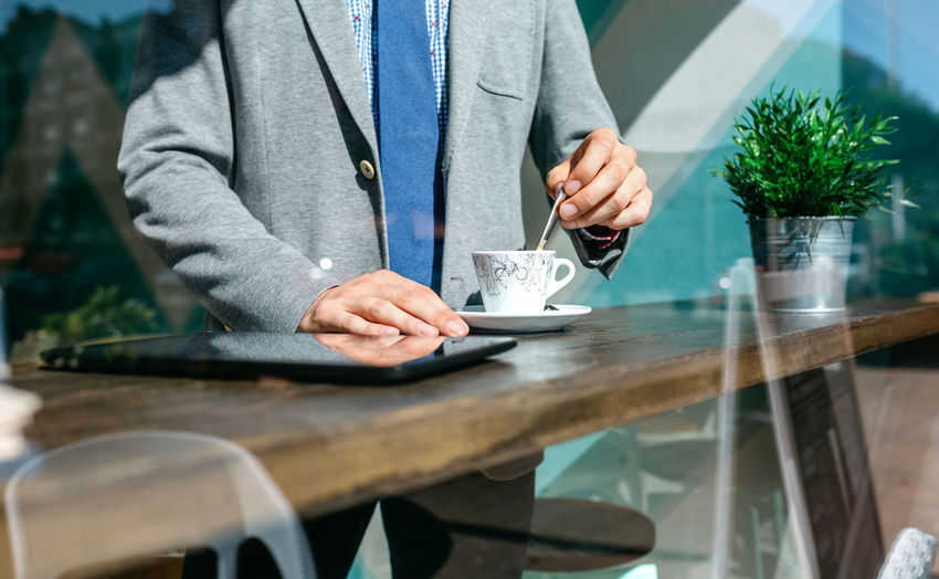 Midsection of businessman with drink standing at table in office