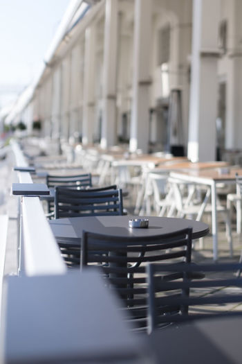 Empty chairs and tables in restaurant against building