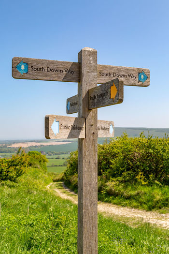 A directional signpost along the South Downs Way in Sussex South Downs Arrow Symbol Clear Sky Communication Day Direction Directional Sign Field Grass Green Color Guidance Land Nature No People Outdoors Pathway Plant Sign Sky Sussex Symbol Text Tree Wood - Material Wooden Post