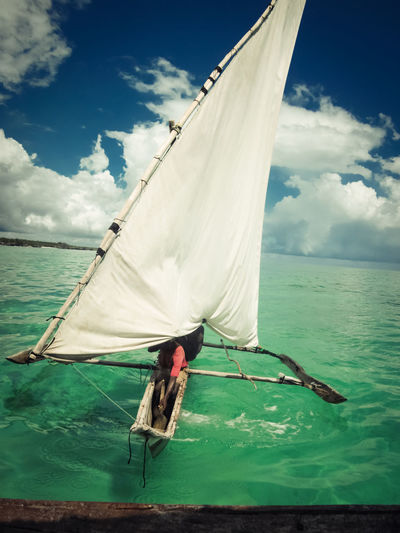 Sailboat in tropical waters Cloud - Sky Water Sea Sky Mode Of Transportation Nautical Vessel Transportation Day Horizon Over Water Horizon Sailing Sailboat Beauty In Nature Outdoors Tranquil Scene Tropical Unrecognizable Person