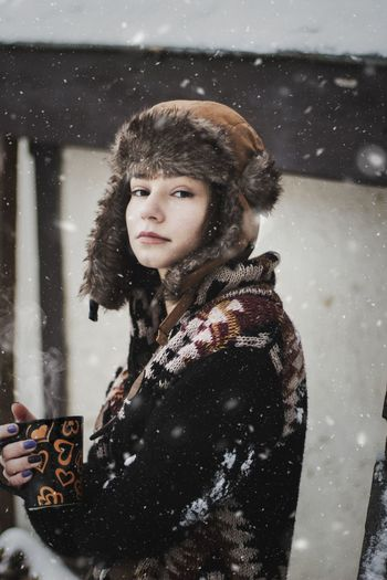 Portrait Of Woman Holding A Cup Of Coffee While It Snows