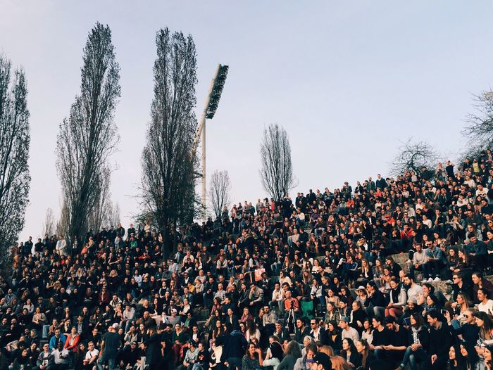 Crowd On Grassy Field Against Sky At Mauerpark