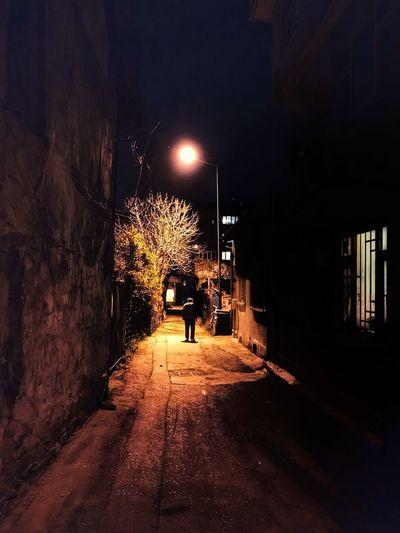 Man in illuminated city at night