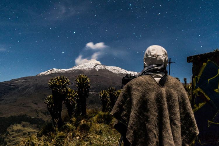Rear view of man standing in desert against star field