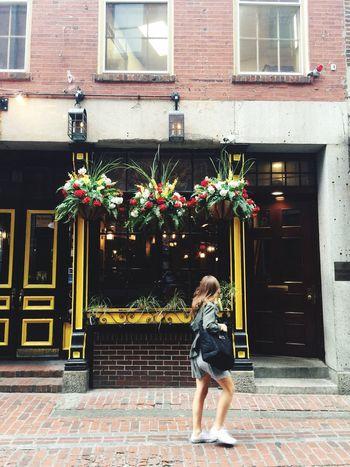 Yellow Building Exterior Woman Walking White Sneakers Doors Boston Flowers Hanging Flowers Long Hair Young Woman Cobblestones Brick Building Boston