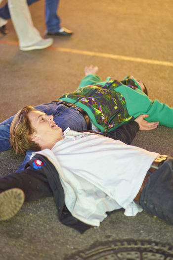 Drunk Men Lying On Road At Amusement Park During Night