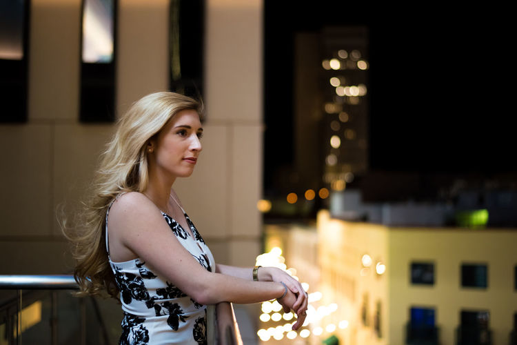 Beautiful young woman standing in balcony at night