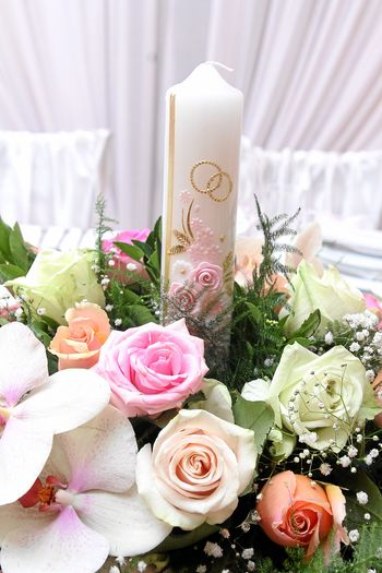 Close-Up Of Candle And Bouquet