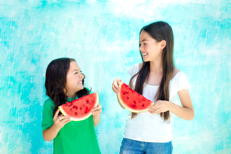 Happy female friends holding watermelon slices against turquoise wall