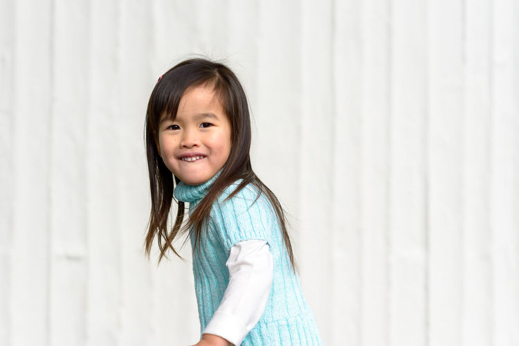 Portrait of smiling girl standing against curtain