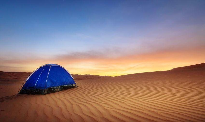 Blue Tent At Desert Against Sky During Sunset