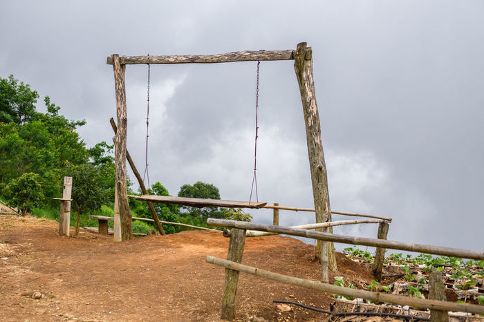 Bamboo fence and wood swing on the mountain in Chiang Mai. Abandoned Absence Architecture Built Structure Cloud - Sky Day Field Jungle Gym Land Metal Nature No People Old Outdoor Play Equipment Outdoors Plant Playground Rusty Sky Tree Wood - Material Wood Swing Wooden Swing