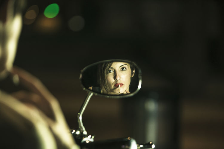Reflection of woman smoking seen in motorcycle mirror
