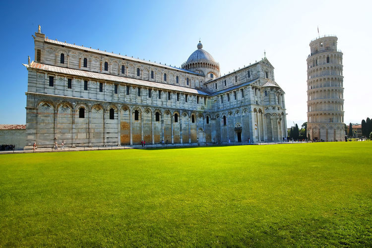 Pisa cathedral by leaning tower against clear sky