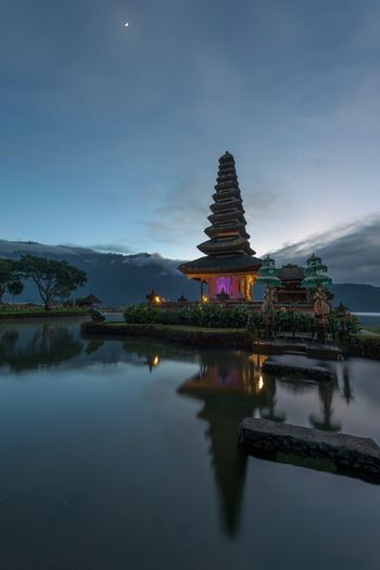 The water temple. The stars were so bright this morning. High up in the mountains of Bali the air is still fresh. The cicle moon reflected her light on the lake as the first light from the sun showed the contours of the horizon. Despite the, less than obvious entrance, we were not the first people on the scene. A local photographer and his partner greeted us from behind their tripod. The water tempel looked amazing. The Danau Bratan is a very popular tourist attraction in the center of Bali. One of the best times to see it, would be just before sunrise at 6am. Danau Bratan Religion Spirituality Architecture Pagoda Place Of Worship Travel Built Structure No People Reflection Travel Destinations Mountain Outdoors Landscape Sunrise Beauty In Nature Night Bali Temple Water Building Exterior Nature ASIA INDONESIA Sky Lost In The Landscape The Traveler - 2018 EyeEm Awards