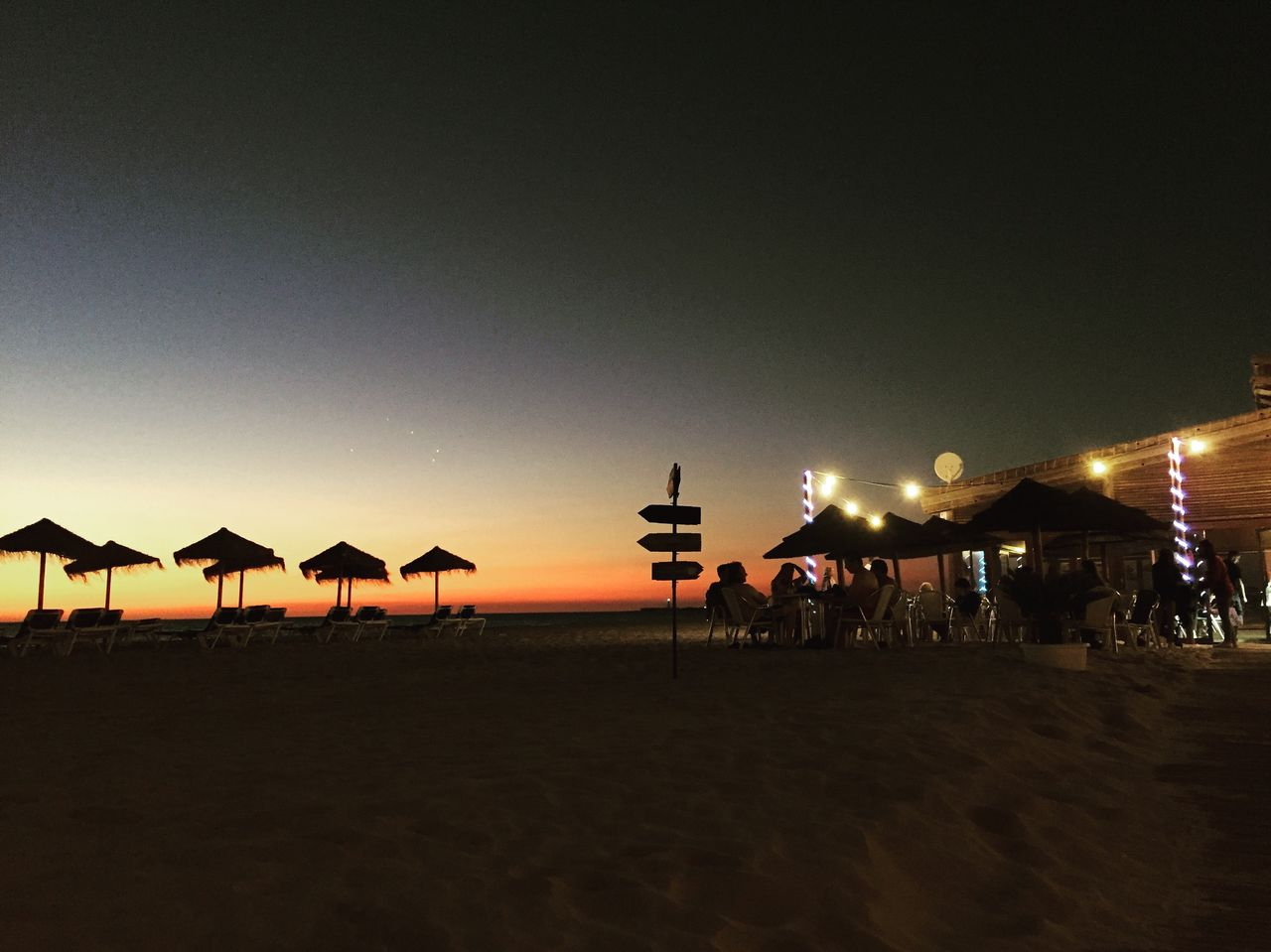 sky, beach, land, sunset, group of people, copy space, nature, sand, illuminated, silhouette, architecture, incidental people, real people, scenics - nature, built structure, large group of people, crowd, night, outdoors, clear sky