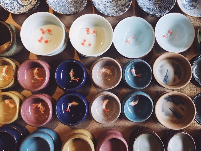 Directly above shot of artificial fish in colorful bowls