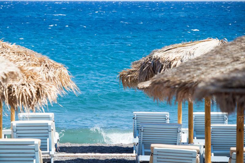 Lounge chairs on beach against sea