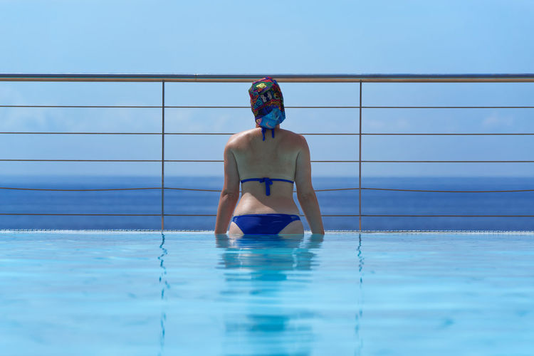 Rear View Of Bikini Woman Looking At Sea While Standing In Infinity Pool