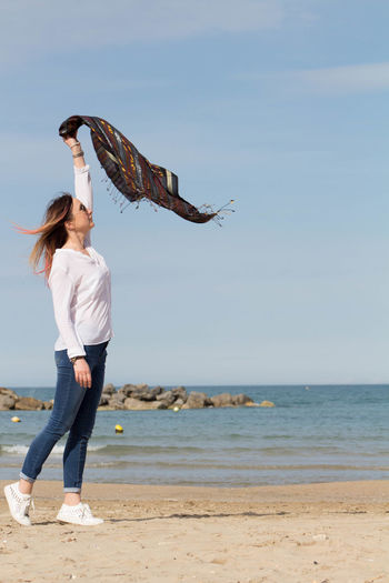 Woman waving scarf while standing on beach against sky