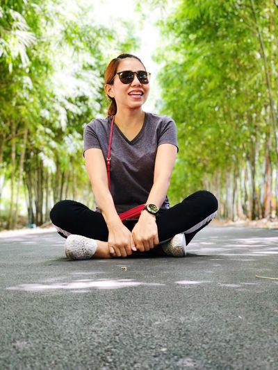 Woman wearing sunglasses while sitting on footpath at park