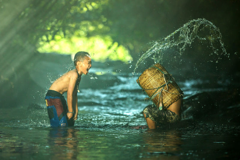 Side view of boy throwing water on man in basket at river