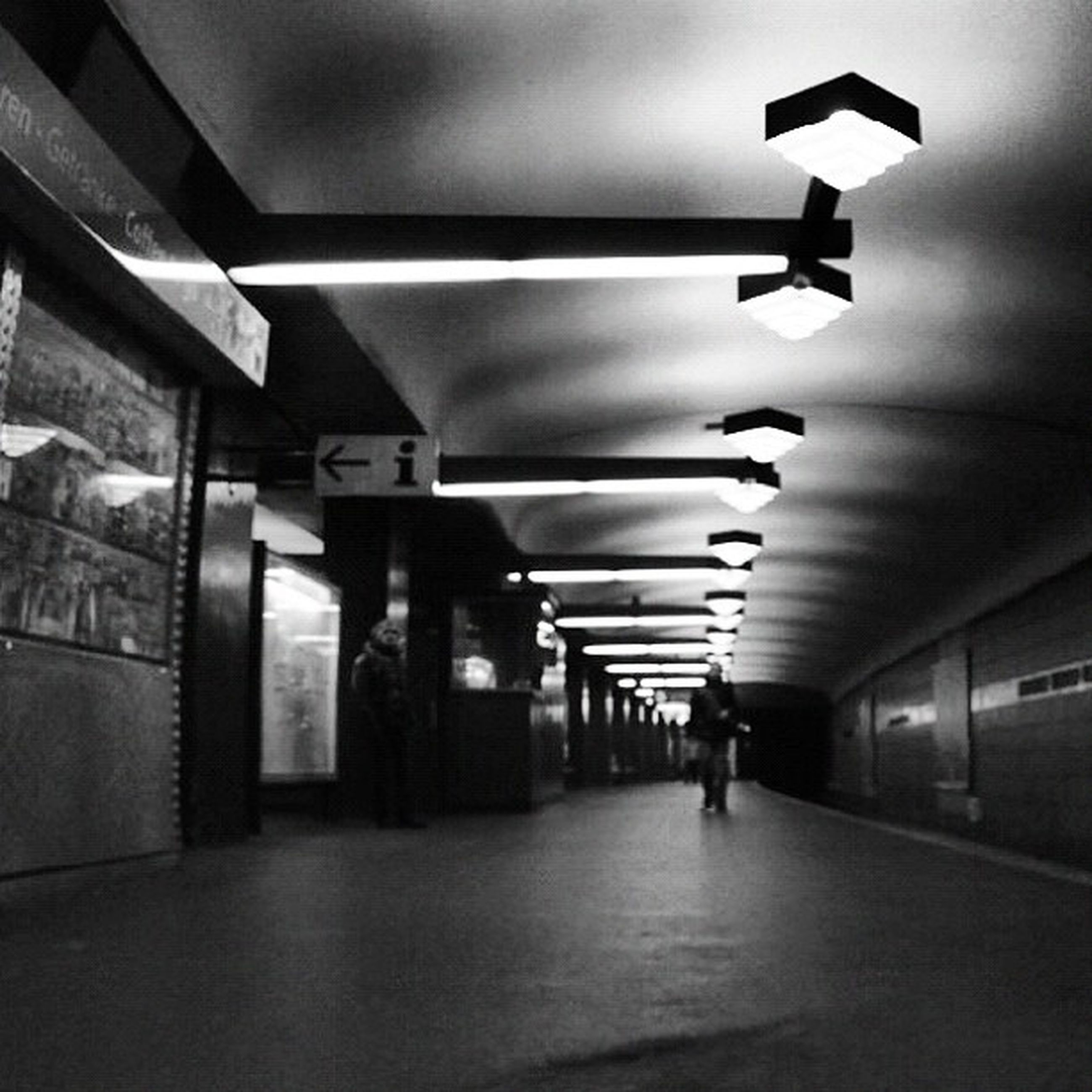 indoors, illuminated, ceiling, lighting equipment, corridor, the way forward, built structure, architecture, subway, wall - building feature, men, subway station, walking, flooring, communication, electric light, diminishing perspective, underground