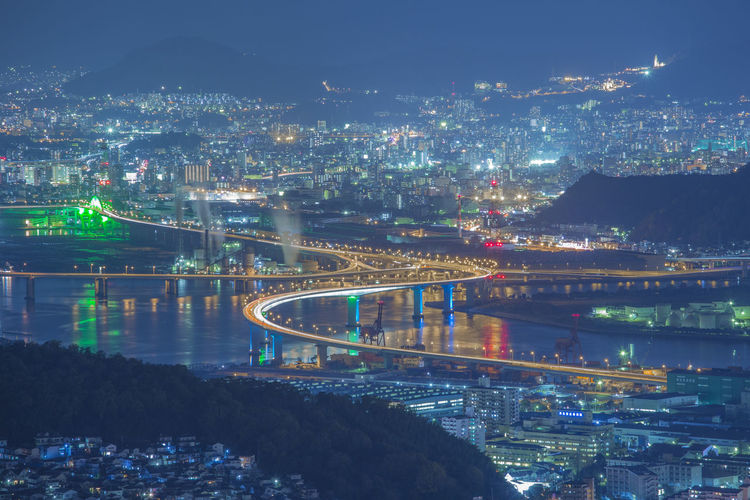 High Angle View Of Illuminated Bridge Over River And Buildings At Night