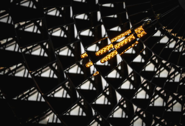 Low angle view of light painting on metal fence