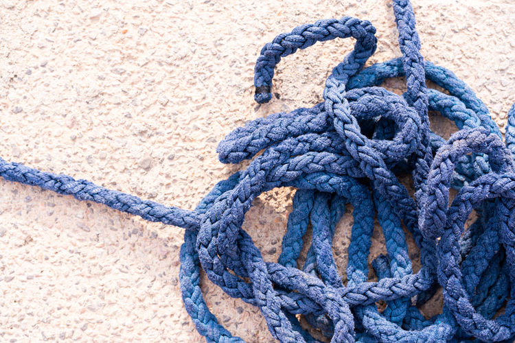 Close-up of rope tied up against blue wall