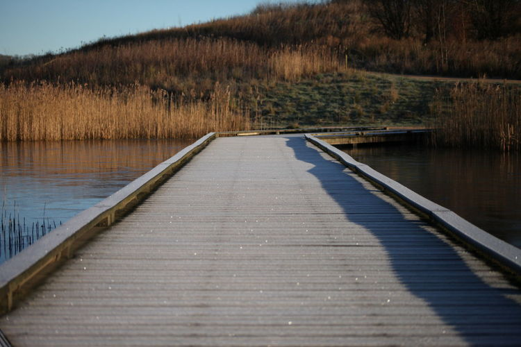 Boardwalk by lake against sky