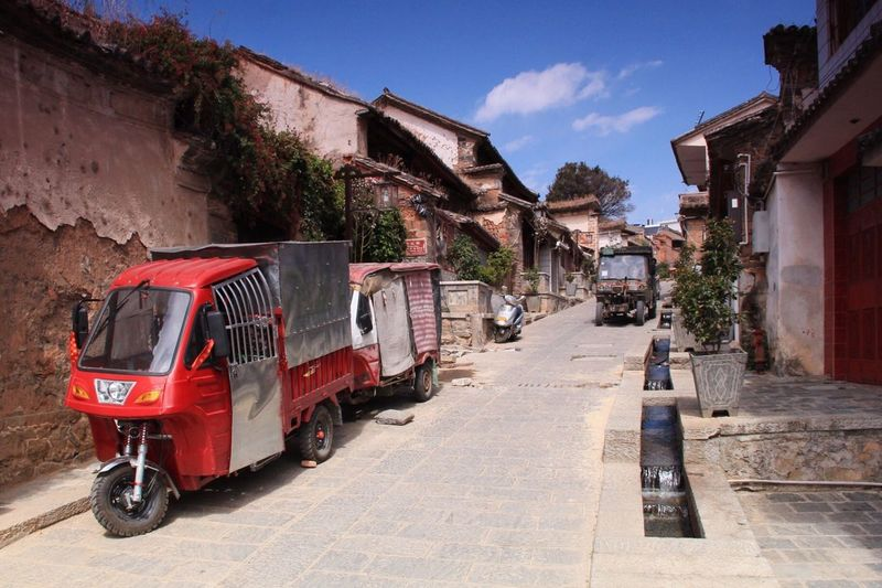 Jinrikishas parked at street on sunny day