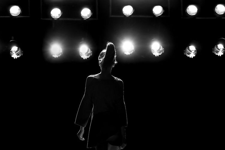 Midsection of woman standing by illuminated lights at night