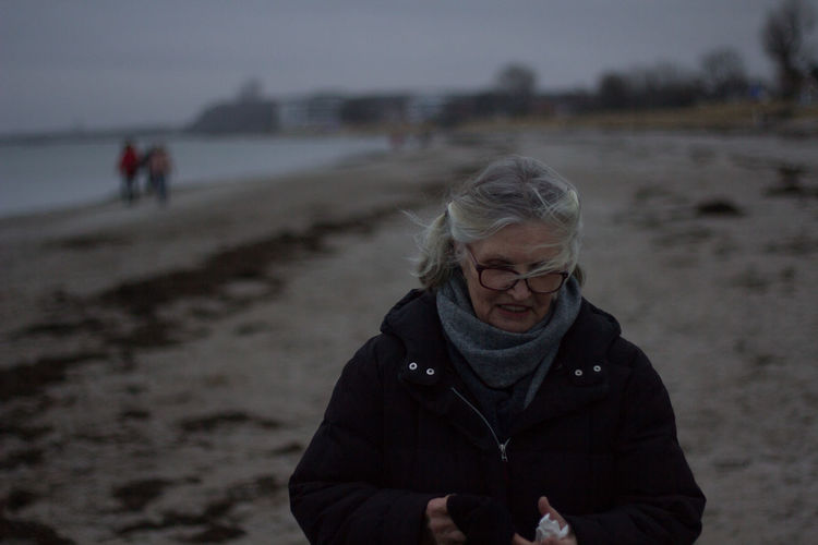 Woman standing at beach during winter