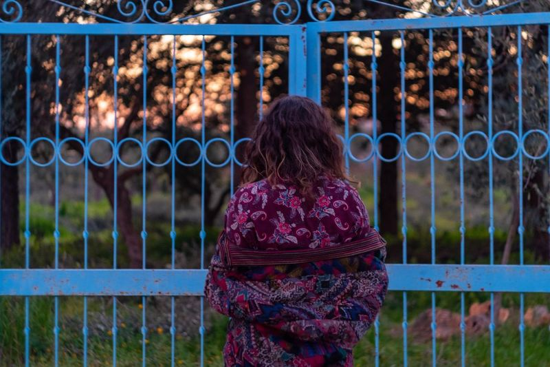 Rear view of woman standing by fence