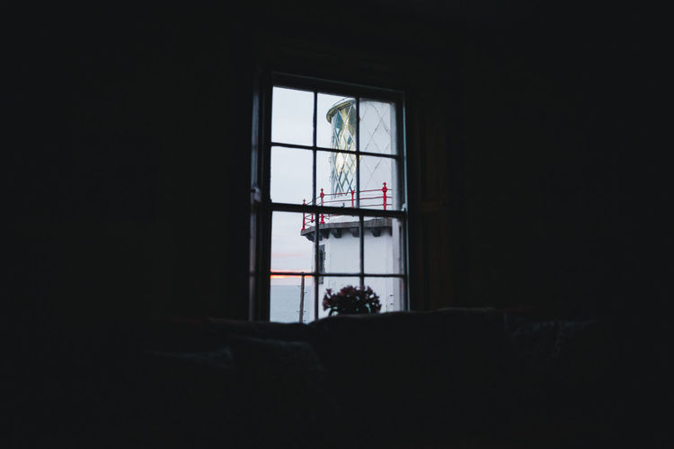 Lighthouse seen through window of dark building