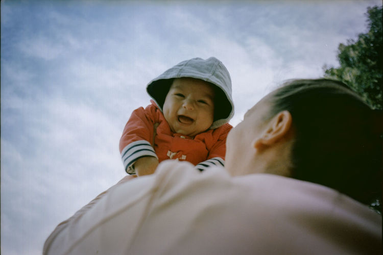 Low Angle View Of Woman Holding Baby