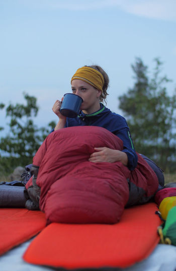 caucasian female hiker drinking beverage from cup while wild camping outdoors Backpacking Camping Coffee Expedition Hiking Hydration Nature Tea Travel Trekking Woman Caucasian Cozy Day Drinking Female Girl Holding Leisure Activity Lifestyles Men Mobile Phone Nature One Person Outdoors Outside People Plant Portrait Real People Red Relaxation Sitting Sky Sleeping Bag Technology Three Quarter Length Warm Clothing Winter Wireless Technology