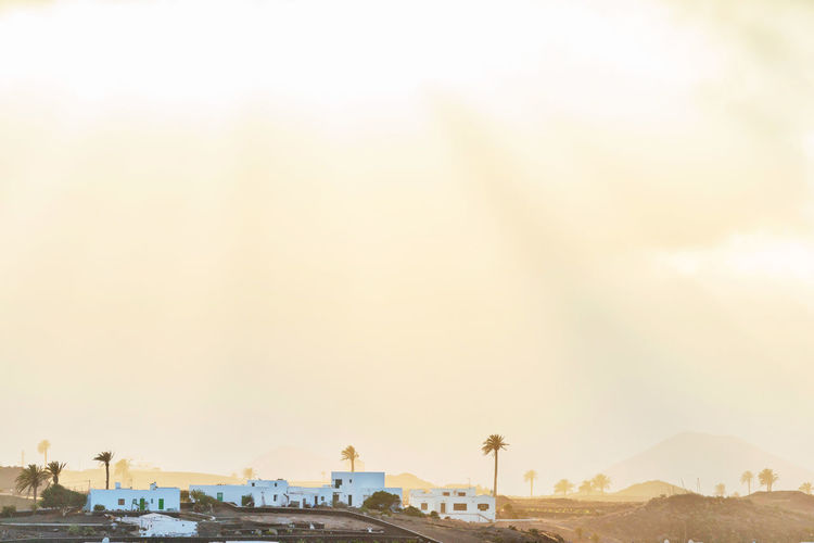 Houses in old town at yaiza against sky during sunset