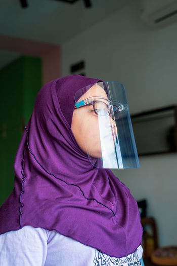 Close-up of woman wearing face shield at home