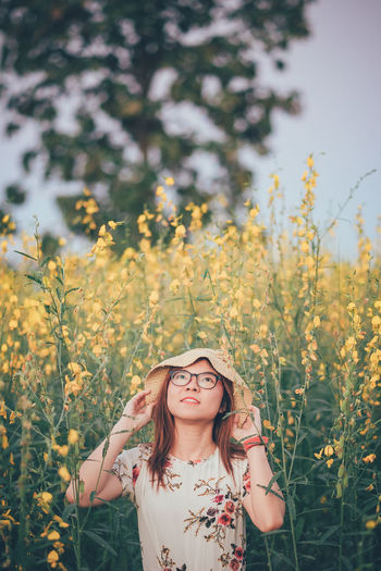 Thoughtful young woman standing amidst yellow flowers on field